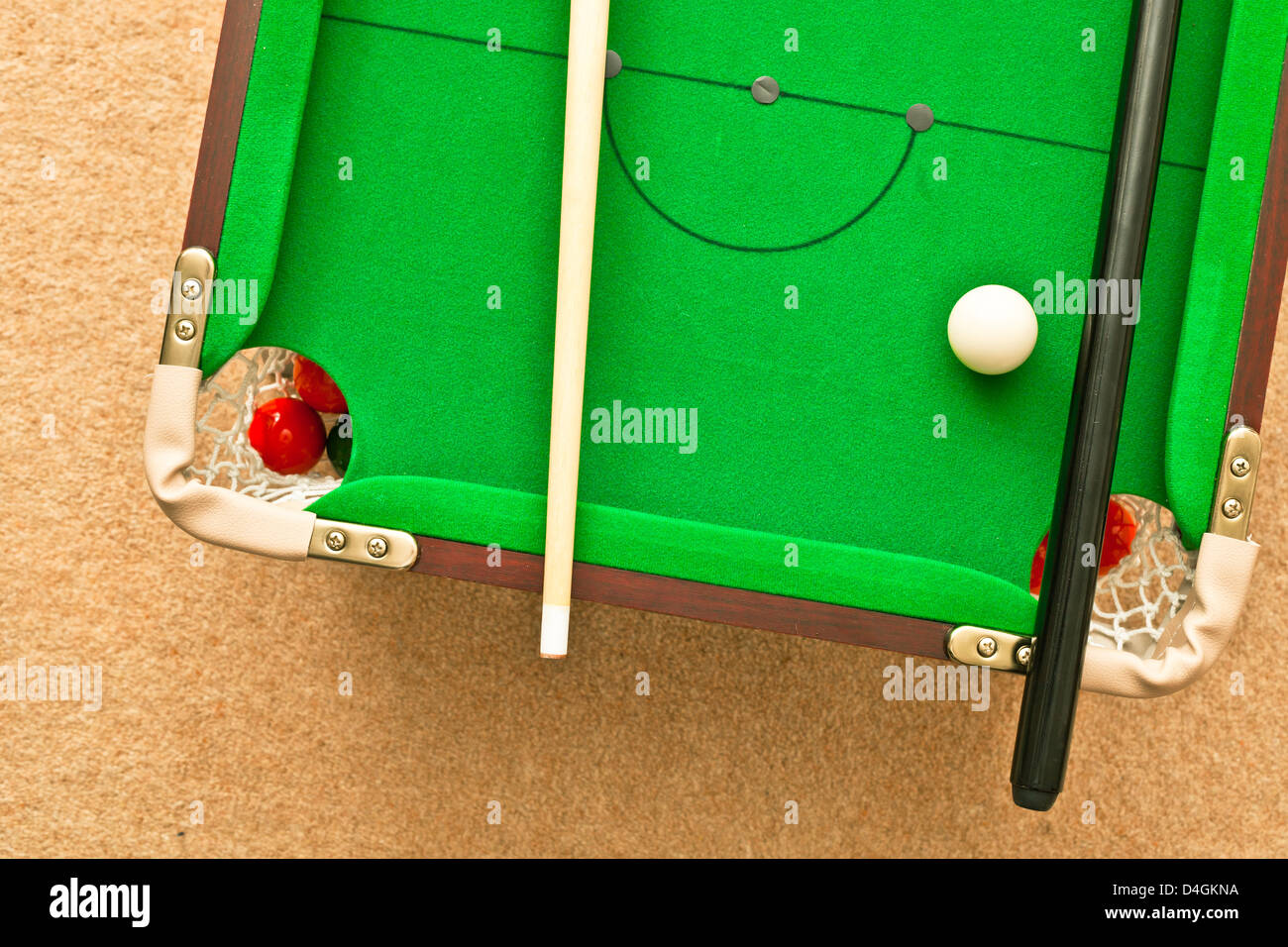 A small pool table on the floor - Stock Image
