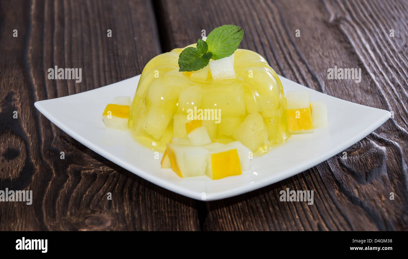 Homemade Honeydew Jello with fruit pieces on wooden background - Stock Image