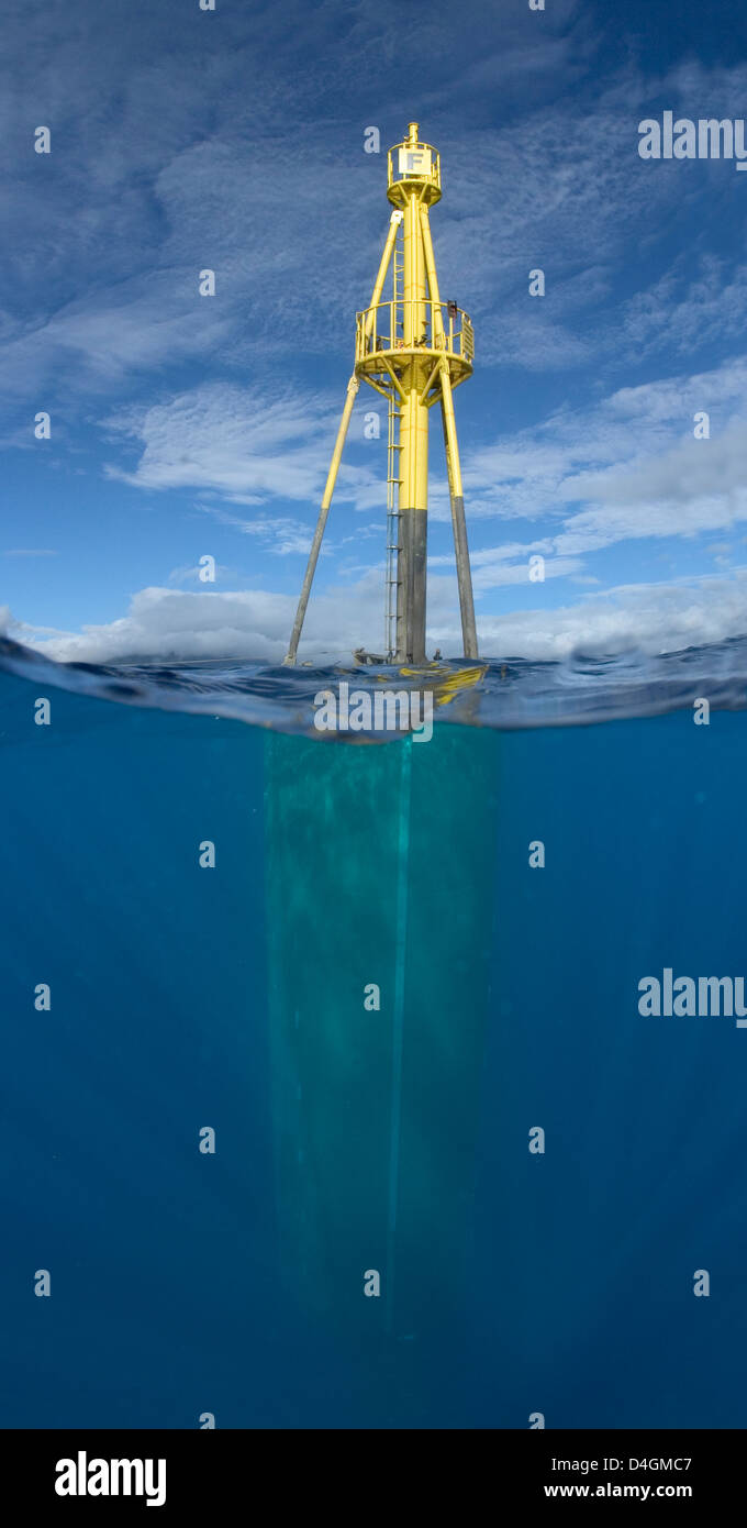 Two images were combined to show this split view of a massive wave energy buoy off Kaneoho Bay, Oahu, Hawaii, USA. - Stock Image