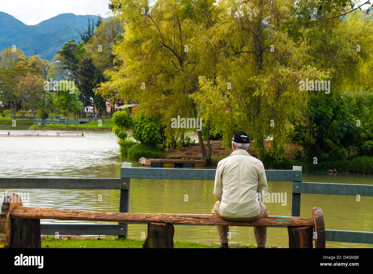 An elderly man sitting on a park bench in Bogota, Colombia - Stock Image