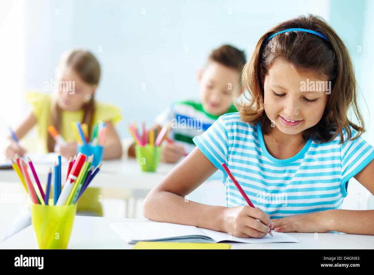 Portrait of lovely girl drawing at workplace with schoolmates on background - Stock Image