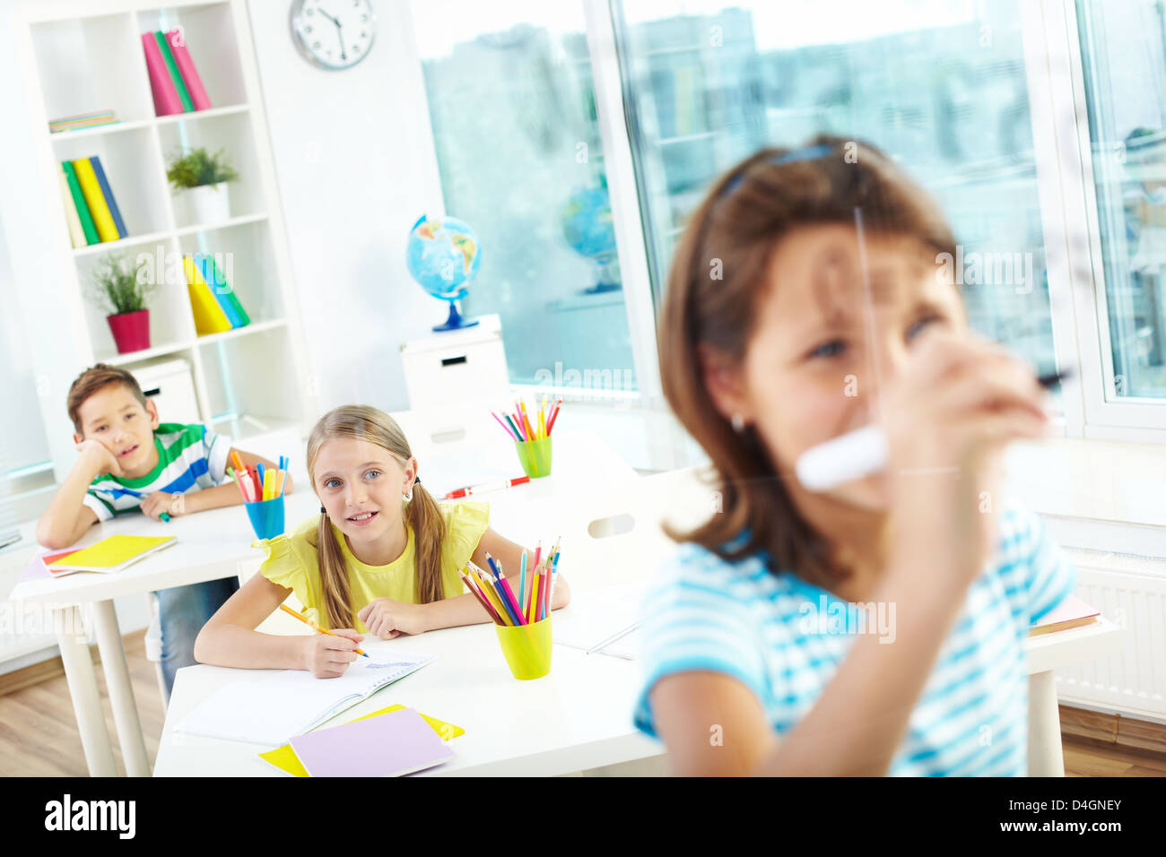 Schoolgirl doing sums on transparent board with two schoolmates looking at her - Stock Image