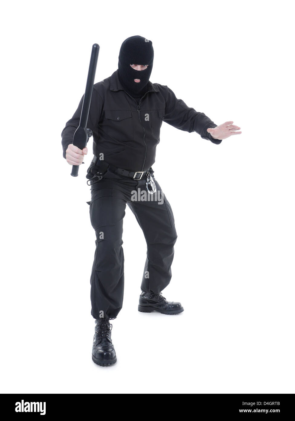 Anti-terrorist police guy wearing black uniform and black mask holding firmly police club in one hand ready for - Stock Image