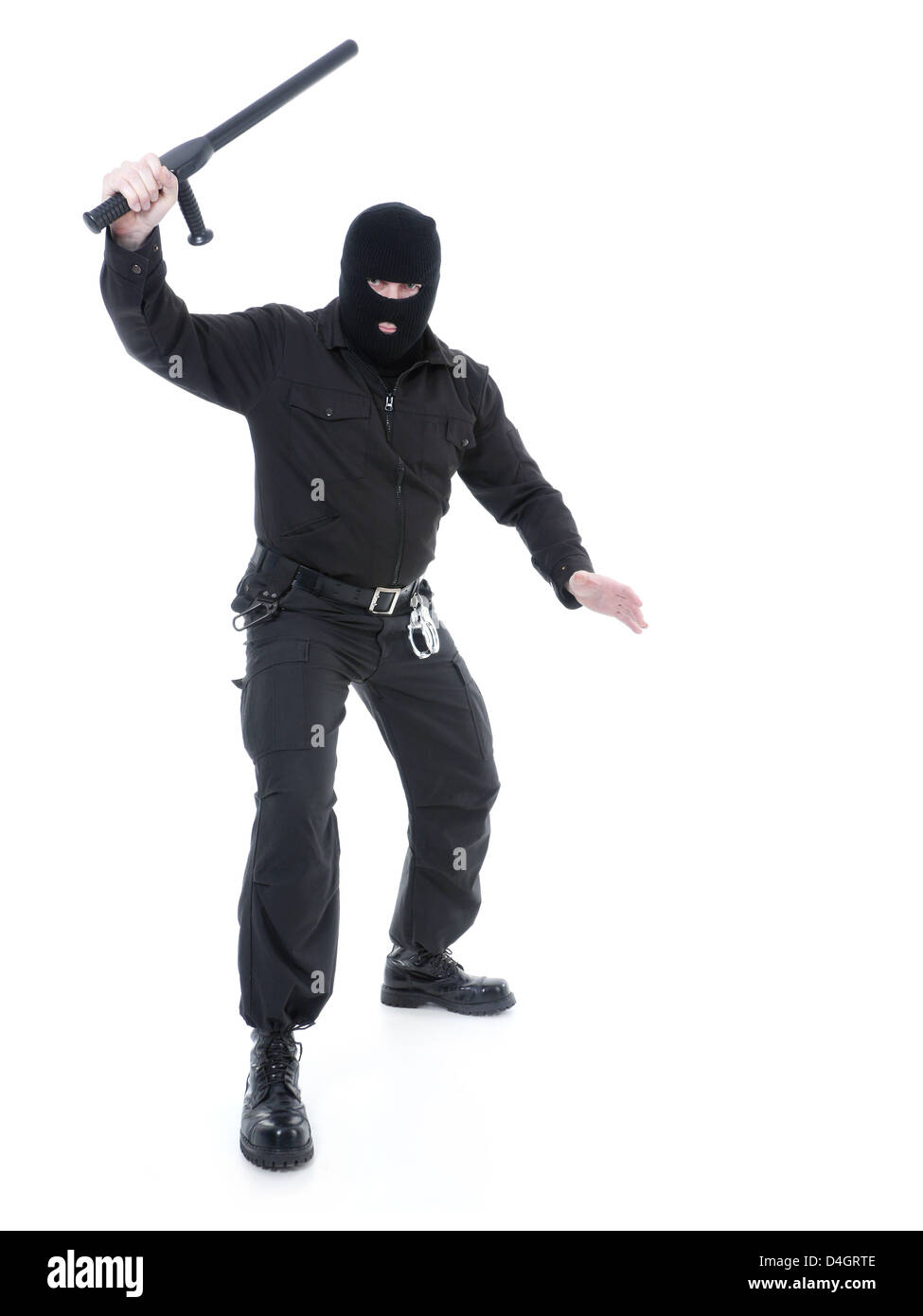Anti-terrorist police guy wearing black uniform and black mask holding firmly police club in one hand raised in - Stock Image