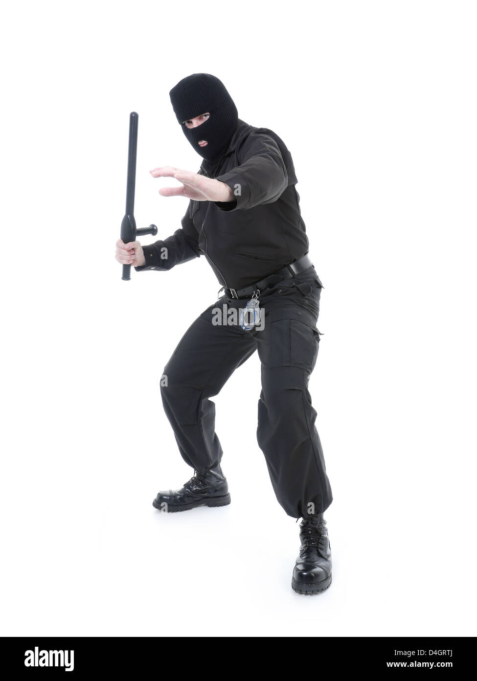 Anti-terrorist police guy wearing black uniform and black mask holding firmly police club in one hand - Stock Image