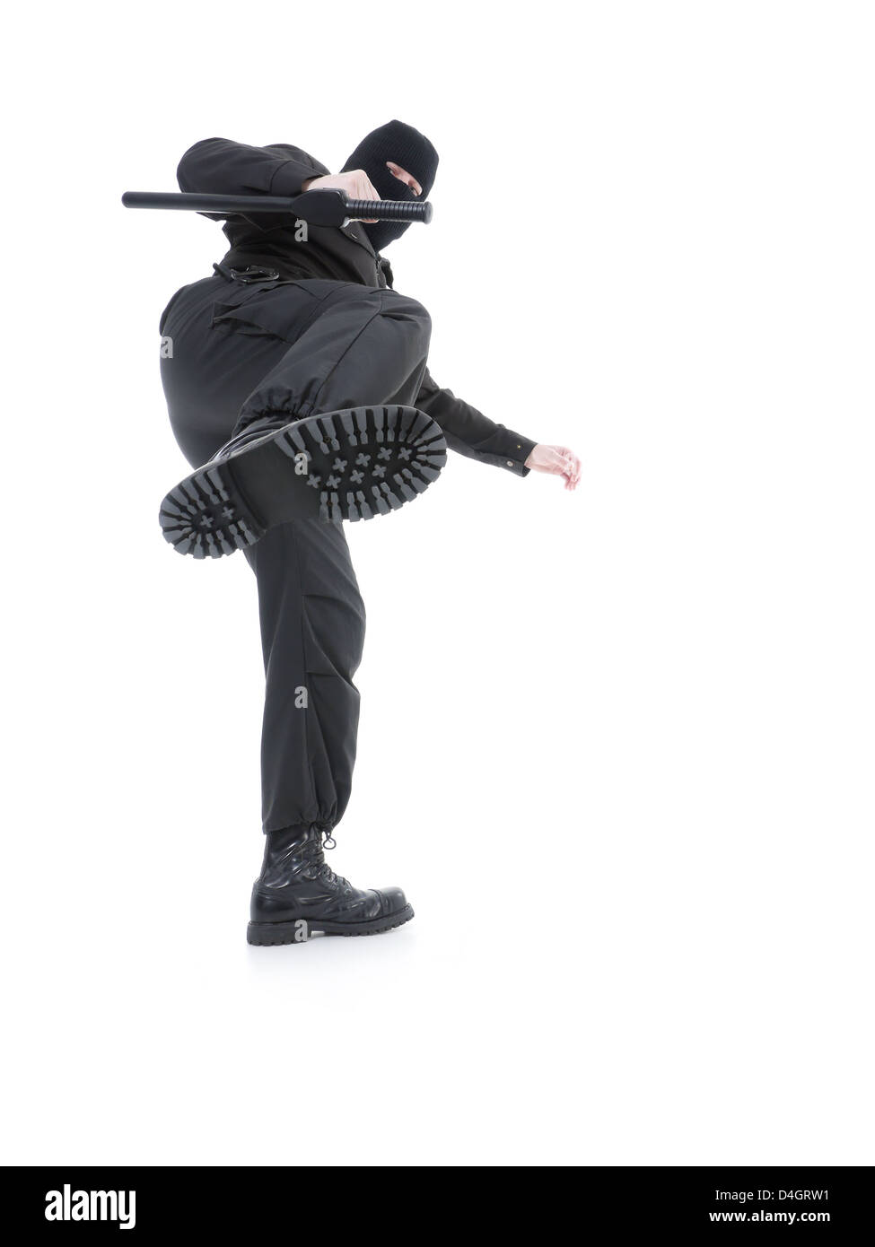 Anti-terrorist police guy wearing black uniform and black mask making a side kick, shot on white - Stock Image