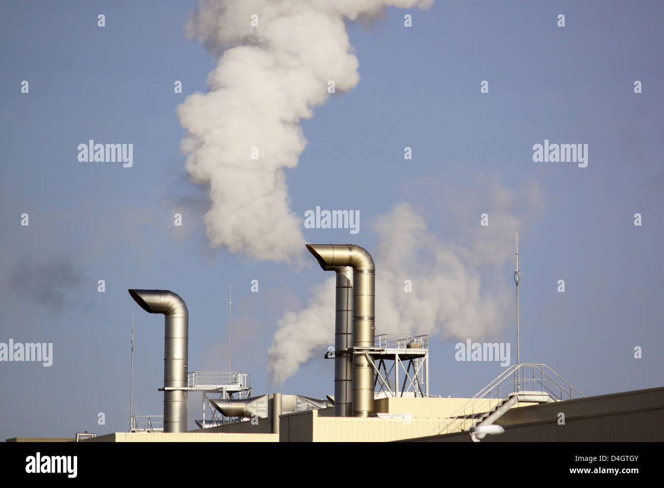 Polluting smoke leaving the chimney of a factory for a productive industry - Stock Image