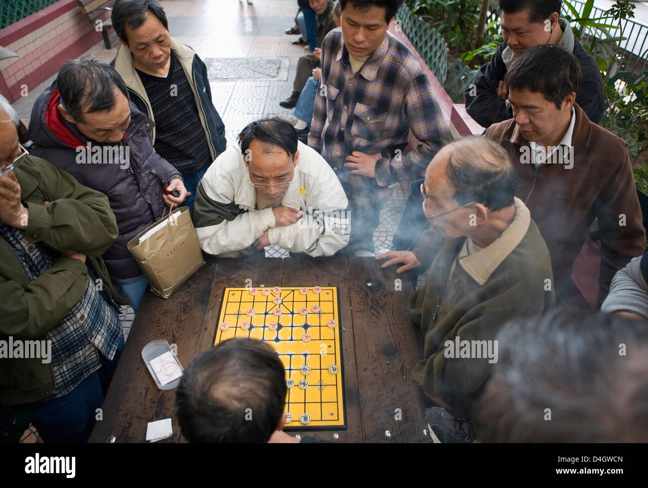 Two Chinese men playing Chinese Chess in the street, other men watching, Hong Kong, China - Stock Image