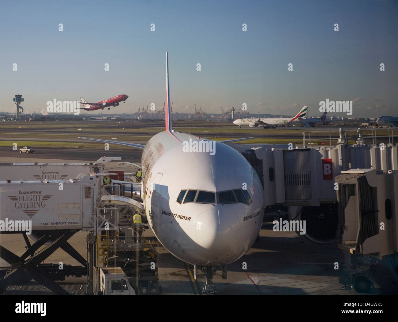 Boeing 777-300 ER jet airliner of Emirates Airline at gate, Emirates and Virgin Blue planes behind, Sydney Airport, - Stock Image