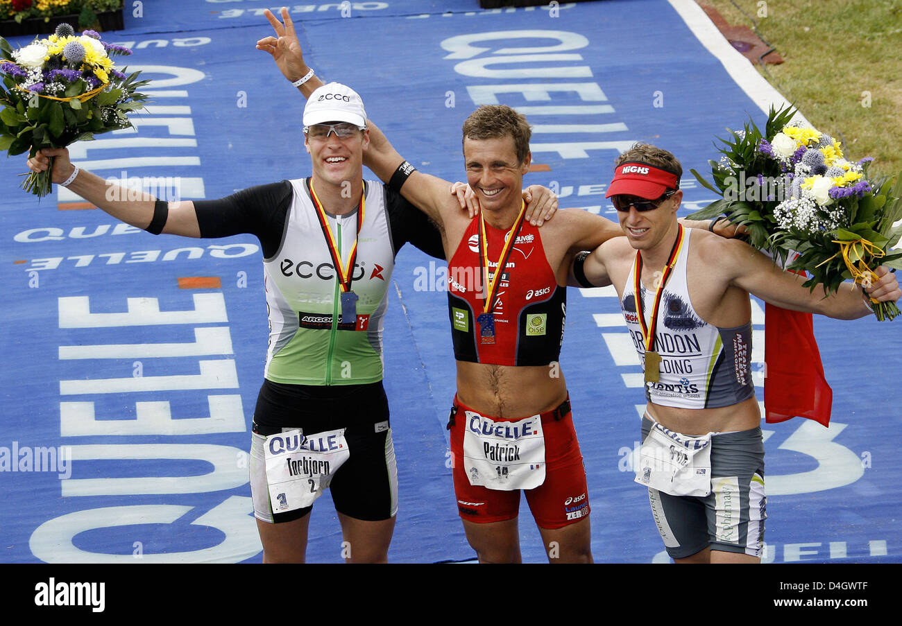 The triathletes Patrick Vernay from New Caledonia (C, 1st place), Pete Jacobs from Australia (R, 2nd place) and - Stock Image