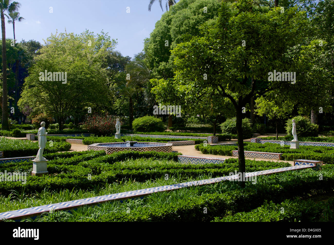 Statues and flower beds, Maria Luisa park, Seville, Andalusia, Spain - Stock Image