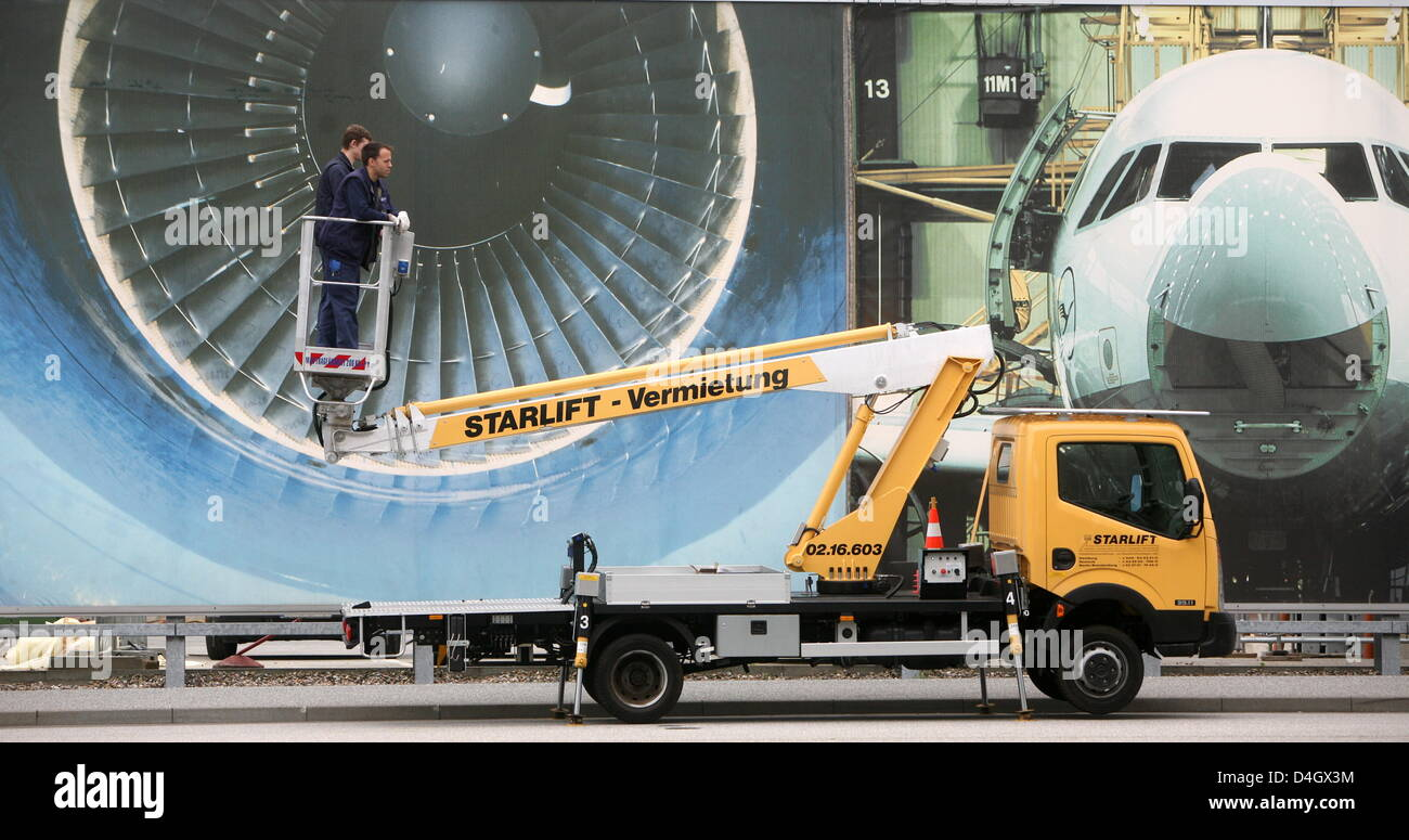 Workers stand on a hydraulic ramp in front of a large scale poster depicting a jet engine on the compounds of the - Stock Image