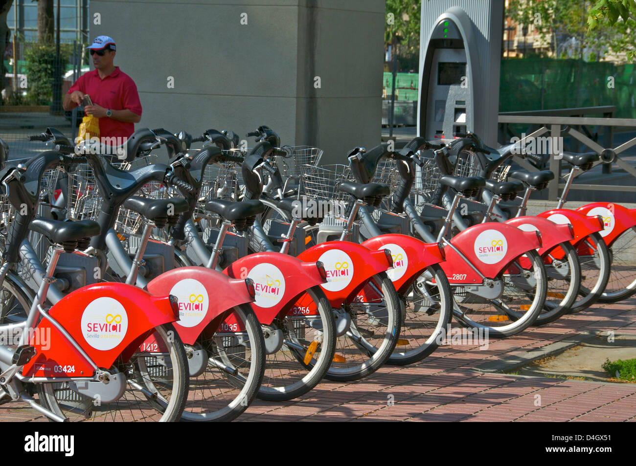 Parked Red Bikes for hire, Seville, Andalusia, Spain - Stock Image