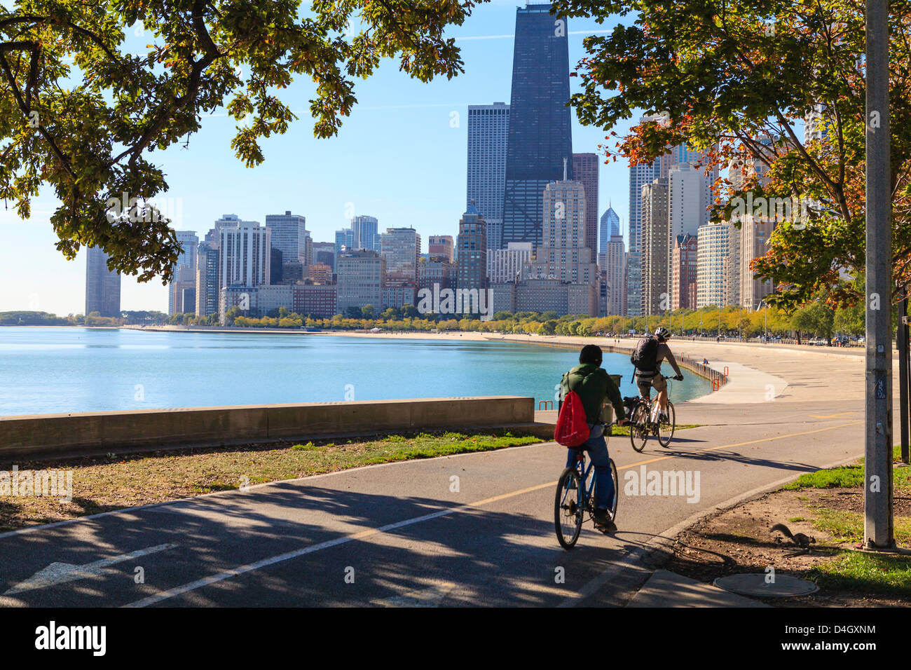 Cyclists riding along Lake Michigan shore with the Chicago skyline beyond, Chicago, Illinois, USA - Stock Image