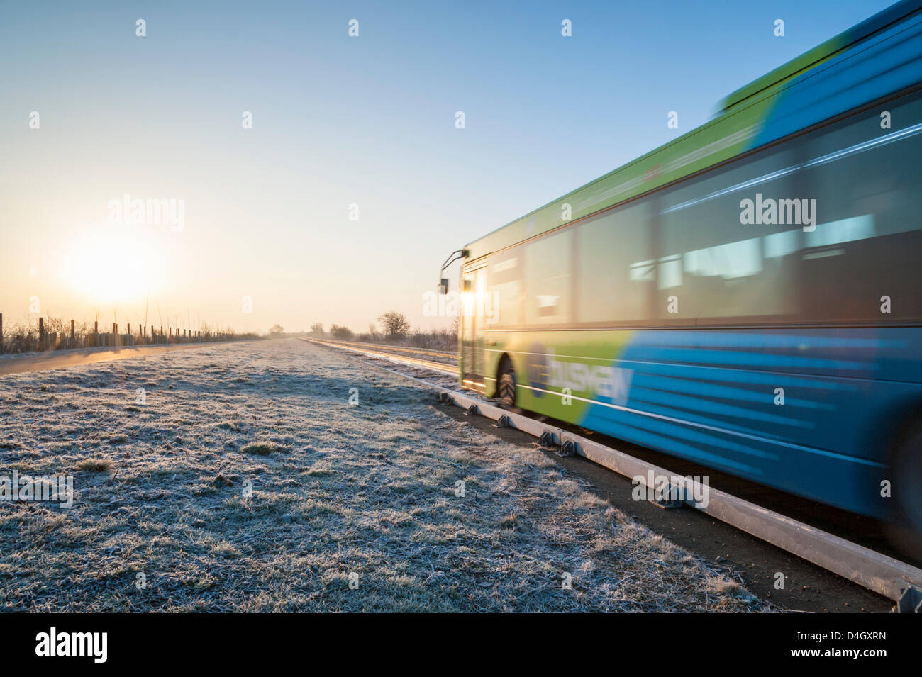 Cambridgeshire, UK. 14th March 2013. A bus carries commuters to Cambridge on the guided busway on a clear frosty - Stock Image