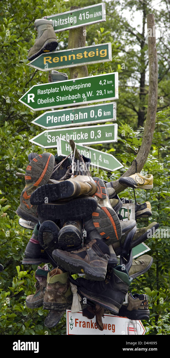 Worn out hiking shoes attached to a sign post at 'kilometre zero', the starting point of famous, 168,3km - Stock Image