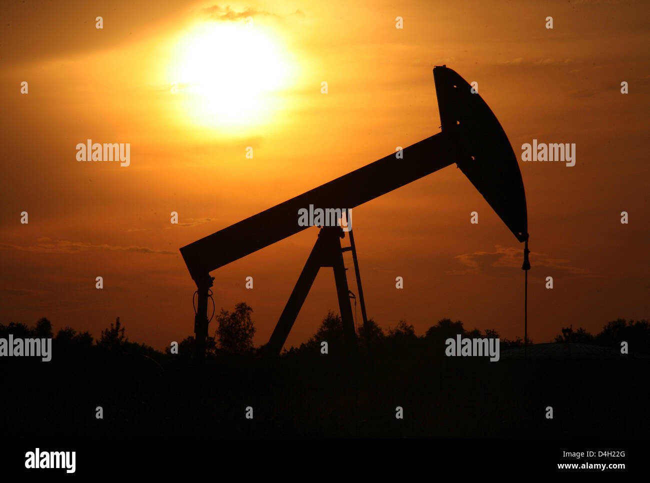 The sun sets behind a pumpjack-type oil pump near Emlichheim, County Bentheim, Germany, 28 July 2008. Since 60 years Stock Photo