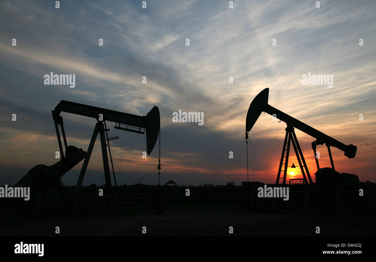 The sun sets behind two pumpjack-type oil pumps near Emlichheim, County Bentheim, Germany, 28 July 2008. Since 60 Stock Photo