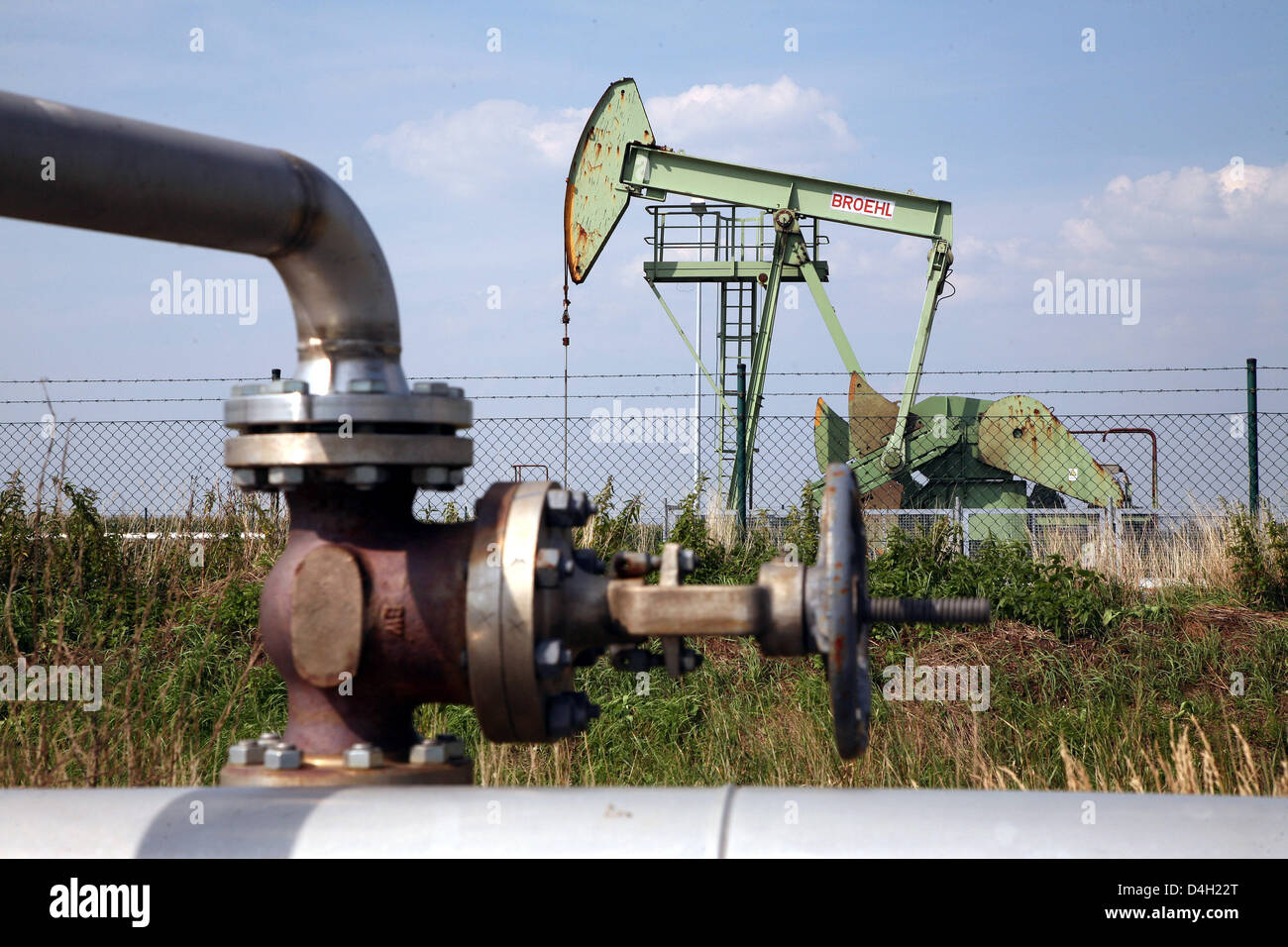 A pumpjack-type oil pump seen behind tubes and a rotary valve near Emlichheim, County Bentheim, Germany, 28 July Stock Photo