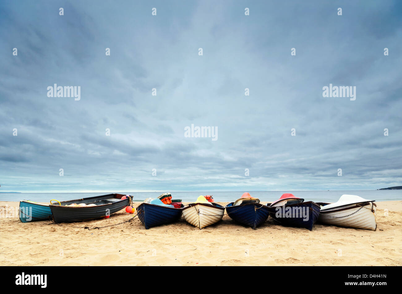 Fishing boats under a brooding sky at Durley Chine on Bournemouth beach. - Stock Image