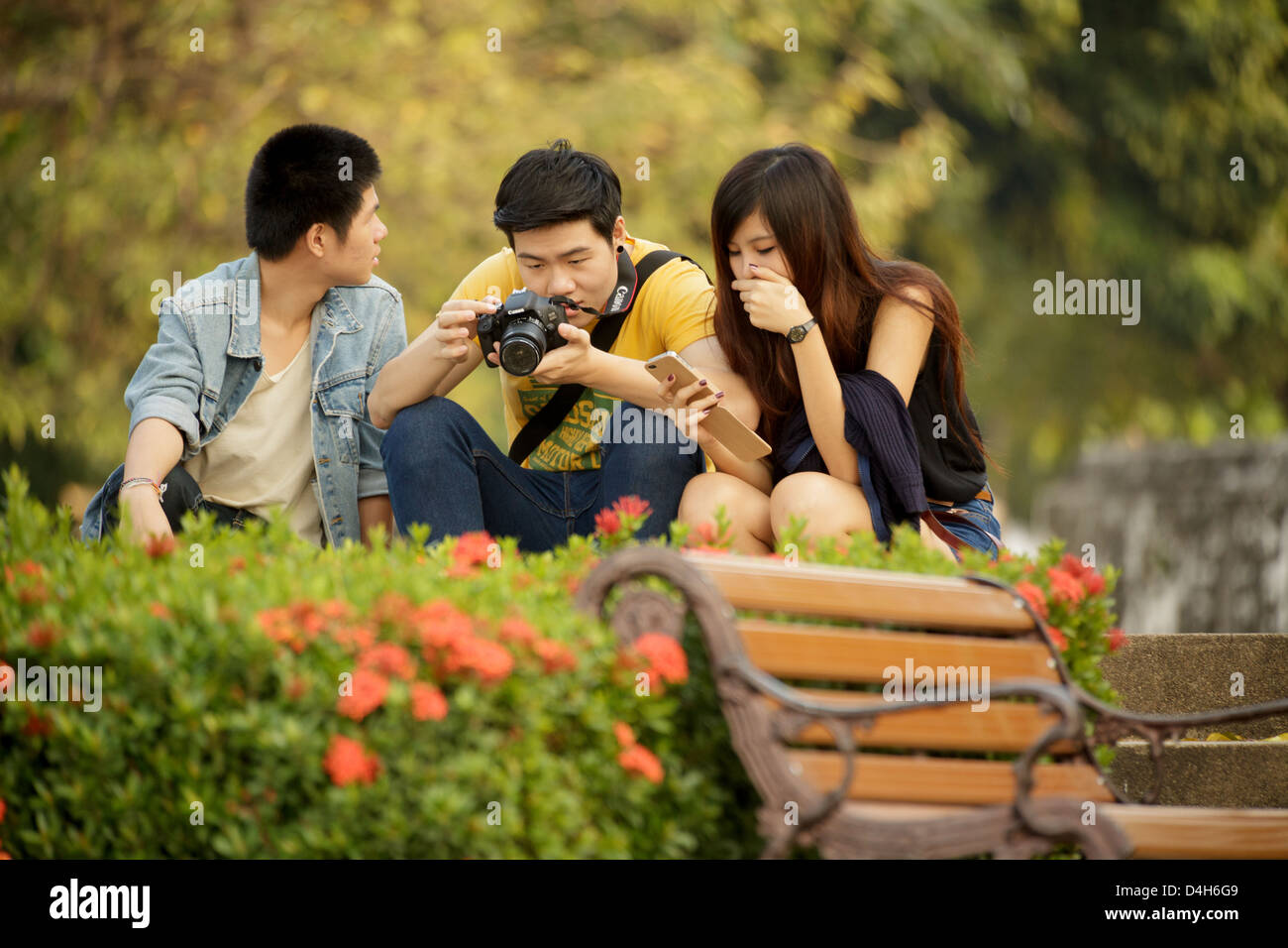 Three people sitting in park, one is  watching the photos on camera, Bangkok, Thailand Stock Photo