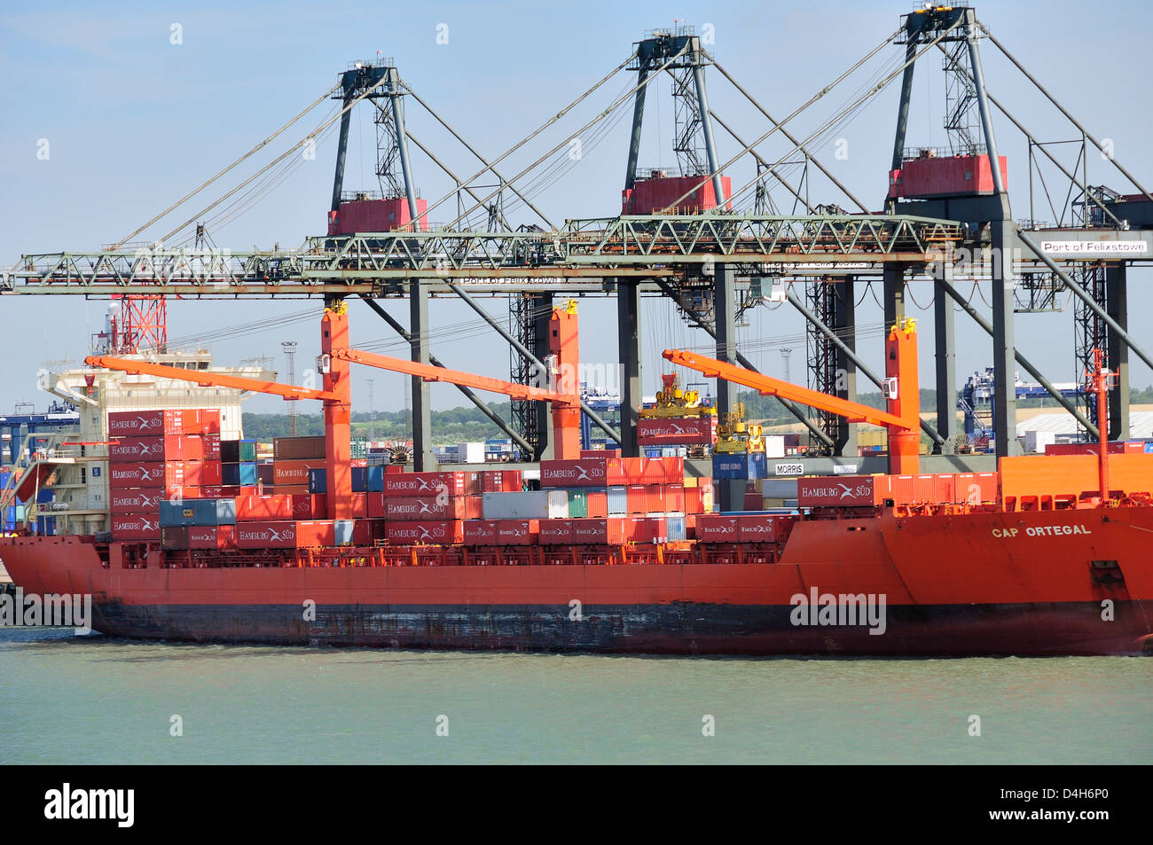 Container being loaded onto container ship by loading derrick at Felixstowe Docks, Suffolk, England, UK - Stock Image