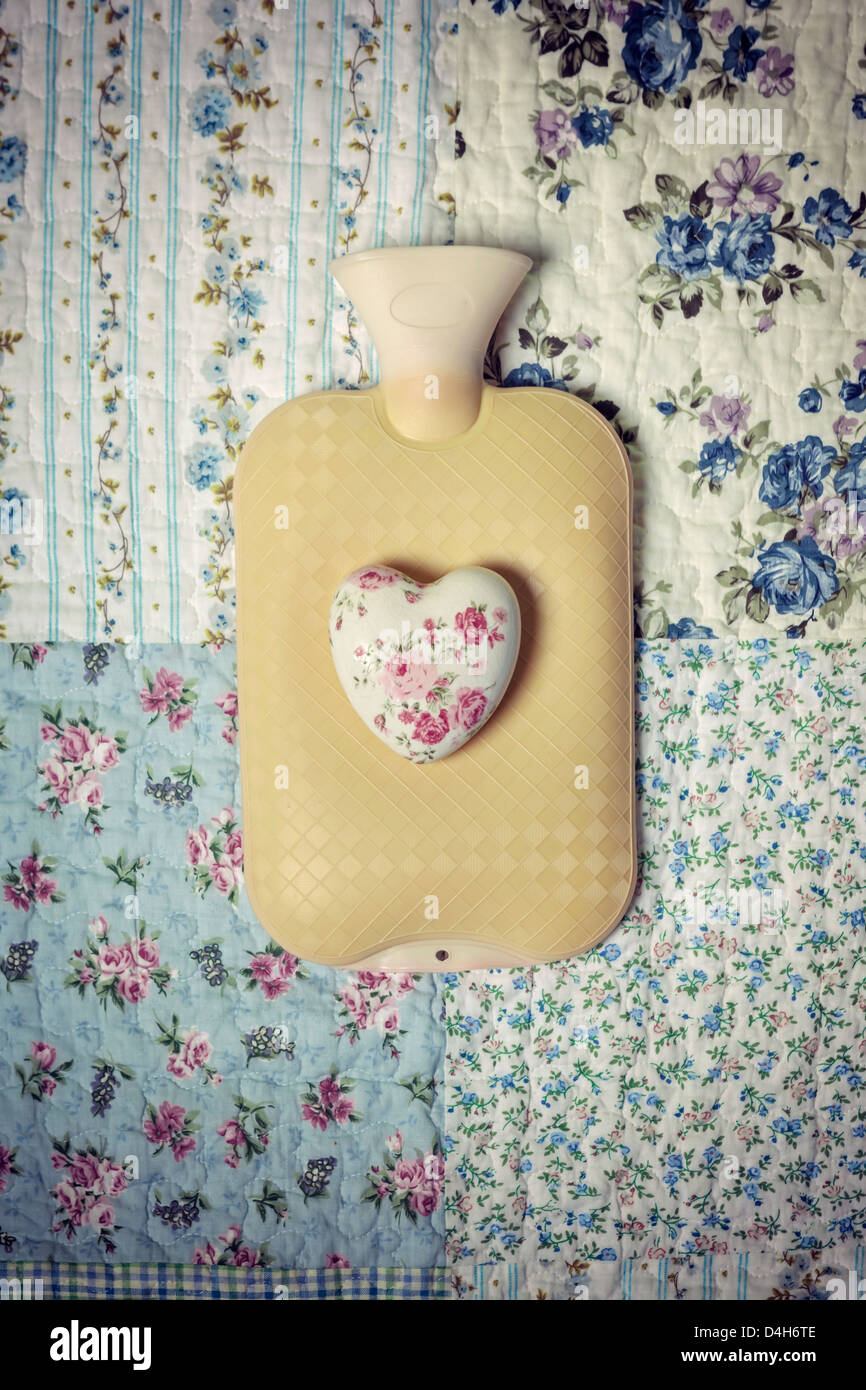 a hot-water bottle on a vintage bed with a floral heart - Stock Image