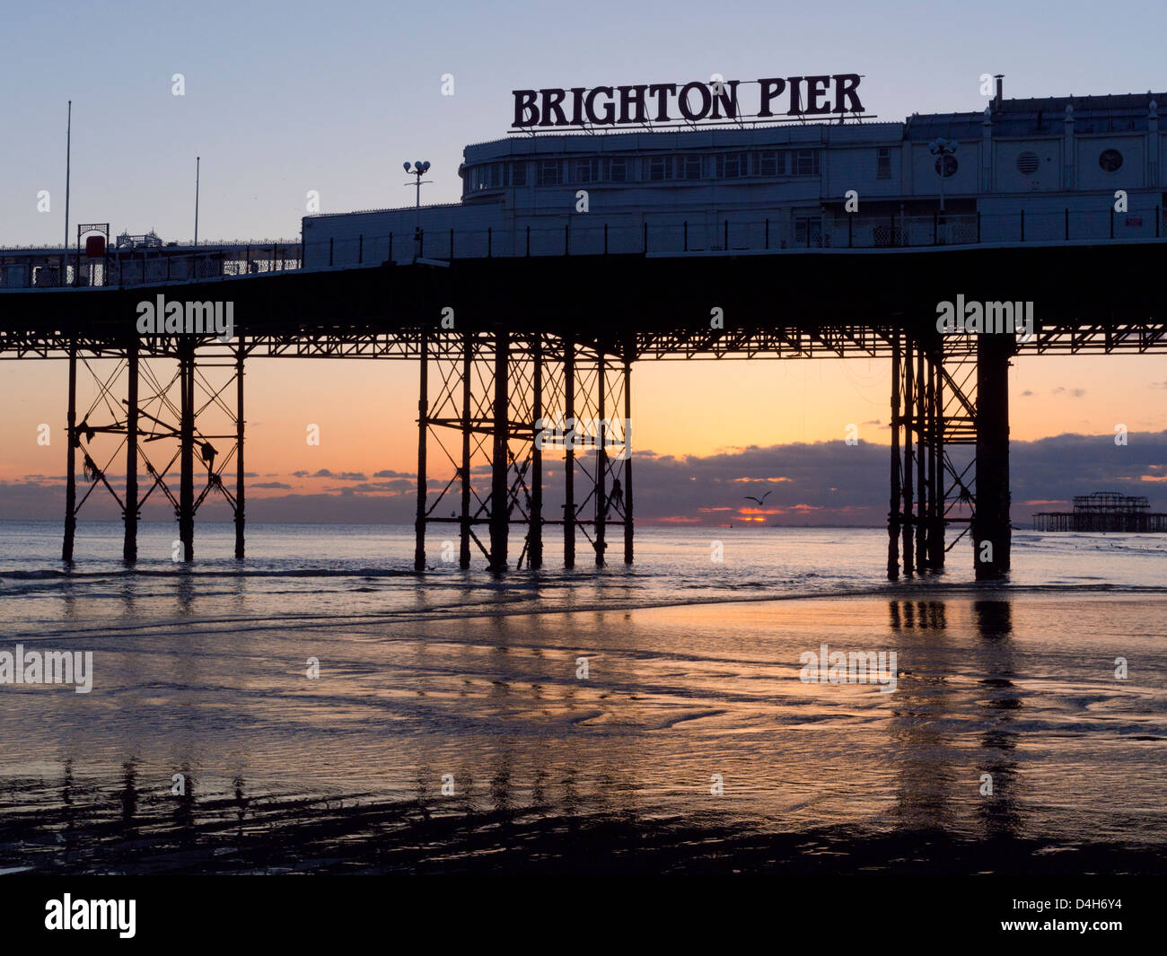 Brighton Pier at sunset, golden sky reflecting off the sand at low tide - Stock Image