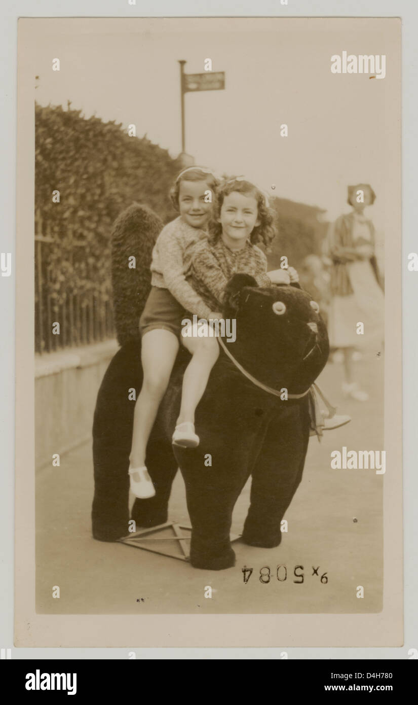 Young girls sitting on a stuffed cat to have their holiday photograph taken at the seaside, Margate,Kent, U.K.  - Stock Image