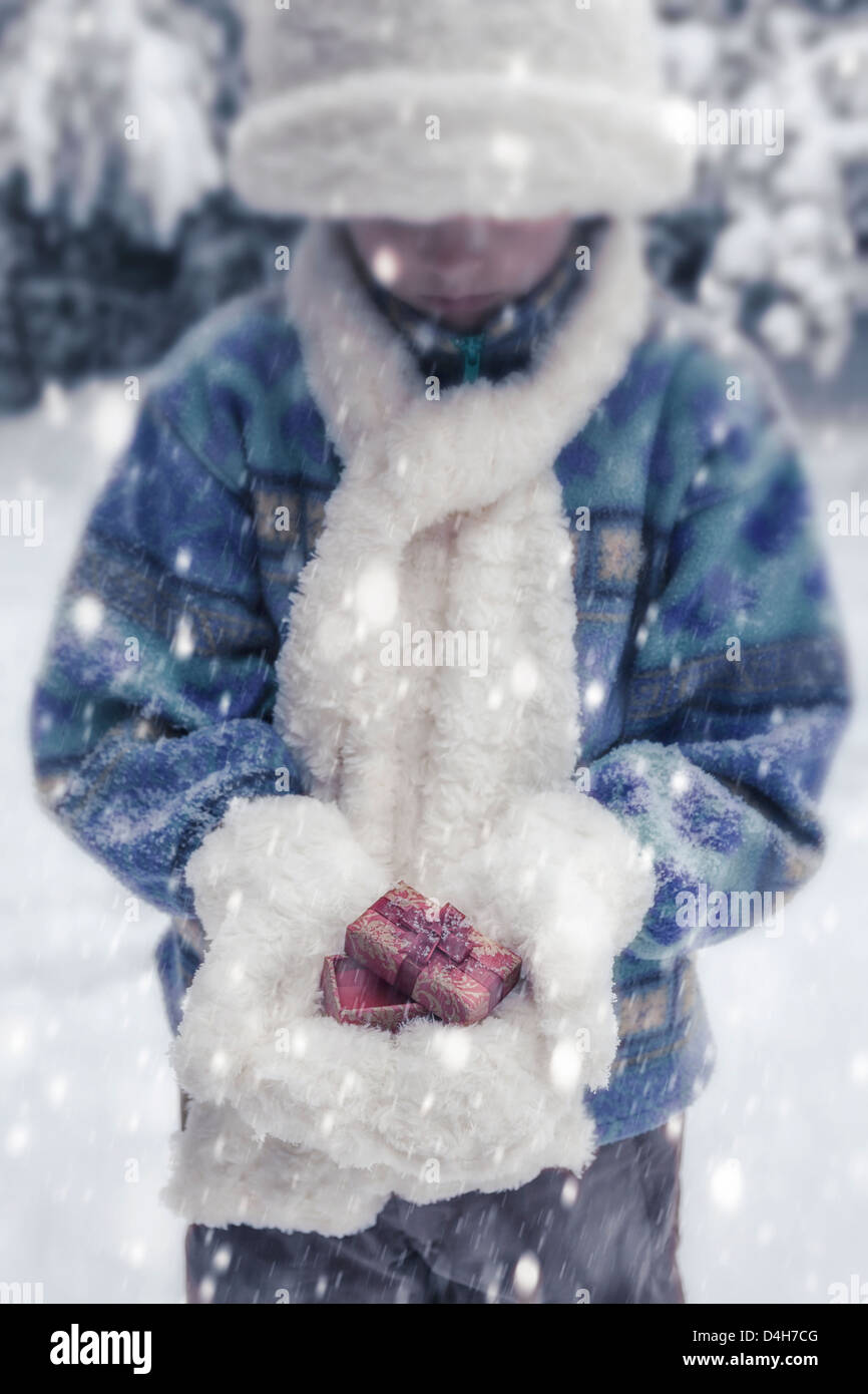 a girl with white hat, scarf and gloves is holding a christmas present - Stock Image