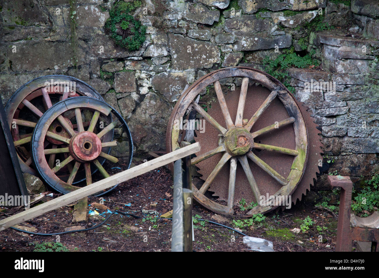 cart wheels, wooden, weathered, old circular saw blade, rusted,decrepit, against old stone wall - Stock Image