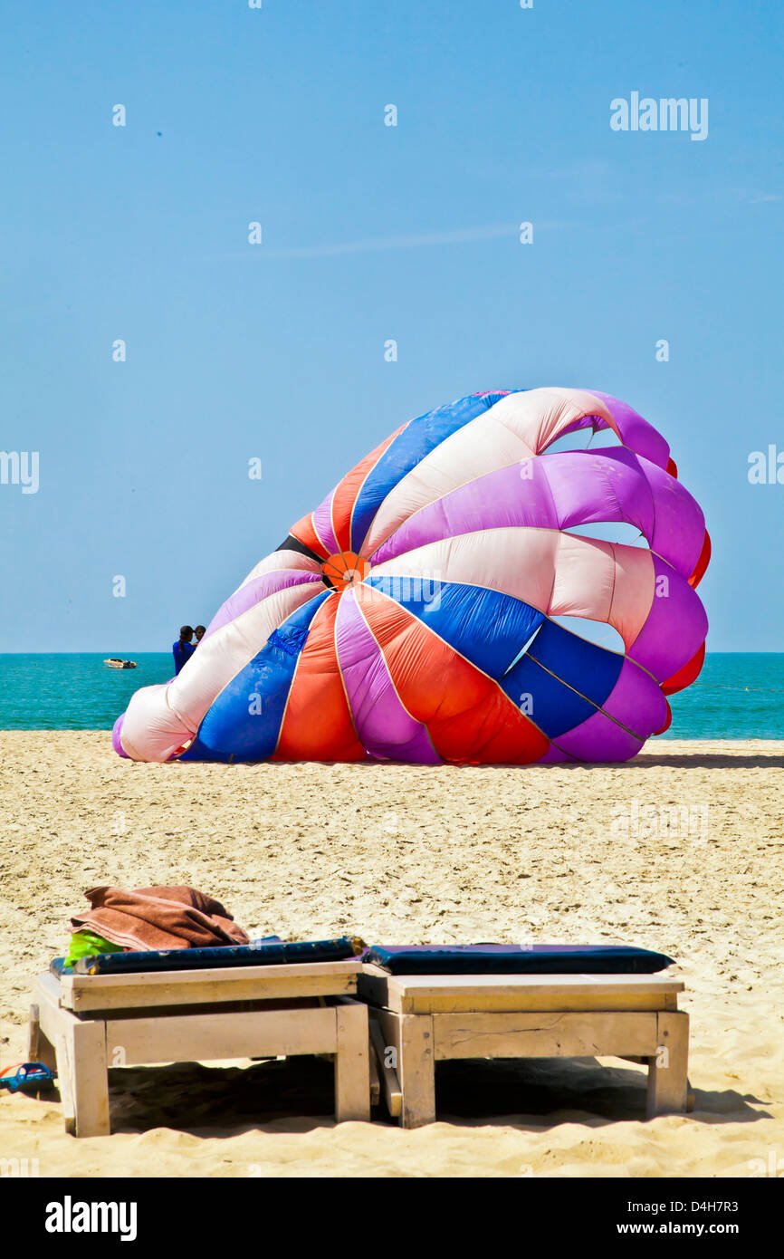 parachute to para glide sand sea blue cloudless tropical sky and assistants assisting customer for next joy ride Stock Photo