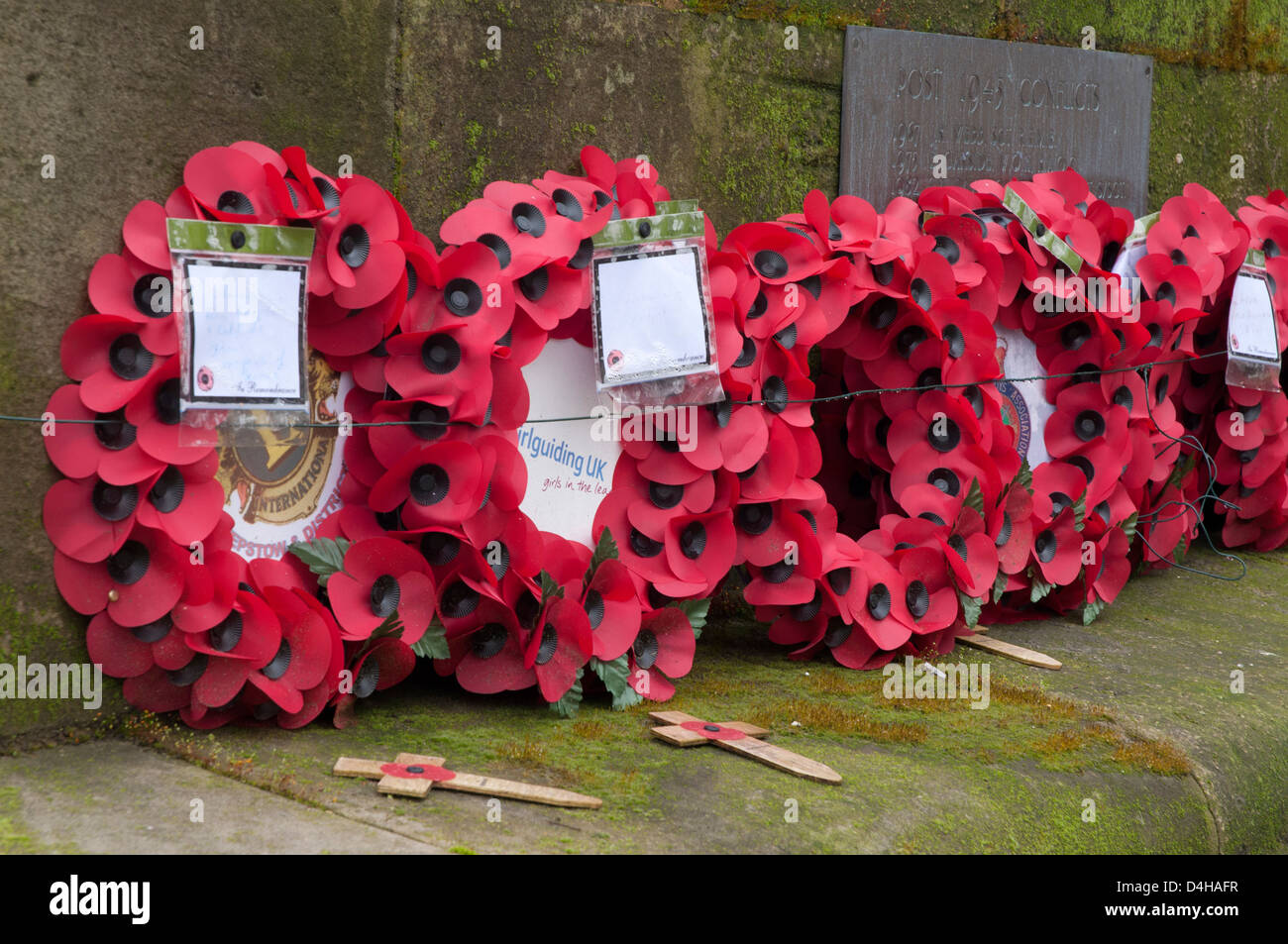 Rememberance Day wreaths laid at town memorial, wet, wintry, emotional , war dead remembered - Stock Image