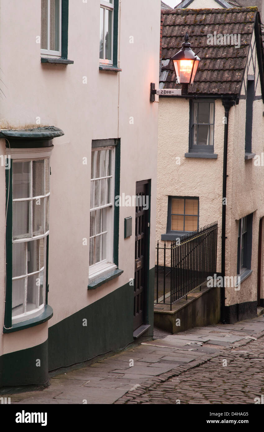 painted cottages in town back street, cobbles,bracketed street lamp, preserved buildings - Stock Image