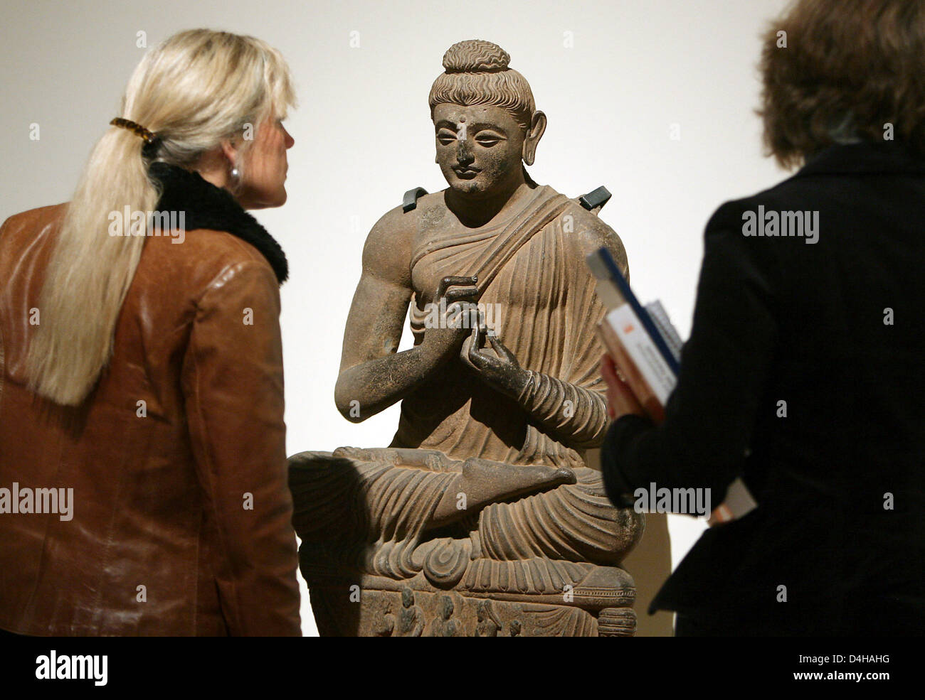Visitors look at a seated Buddha statue on display at the exhibition ?Gandhara - Das buddhistische Erbe Pakistans? - Stock Image