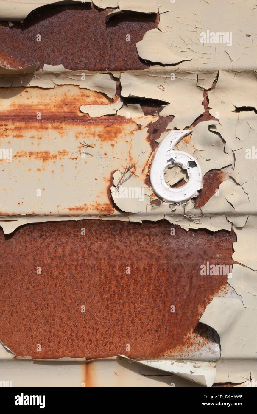 Rusted metal with peeling painwork, decrepit, garage door, - Stock Image