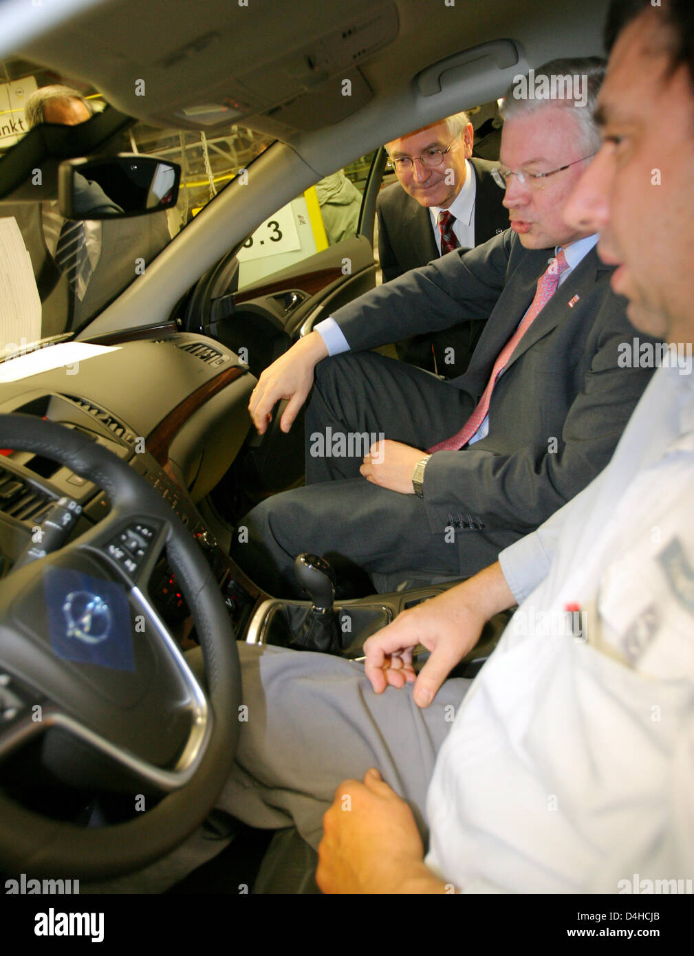 Prime Minister of Hesse, Roland Koch (C) and head of Opel Hans Demant (L) chat with an Opel employee inside the - Stock Image