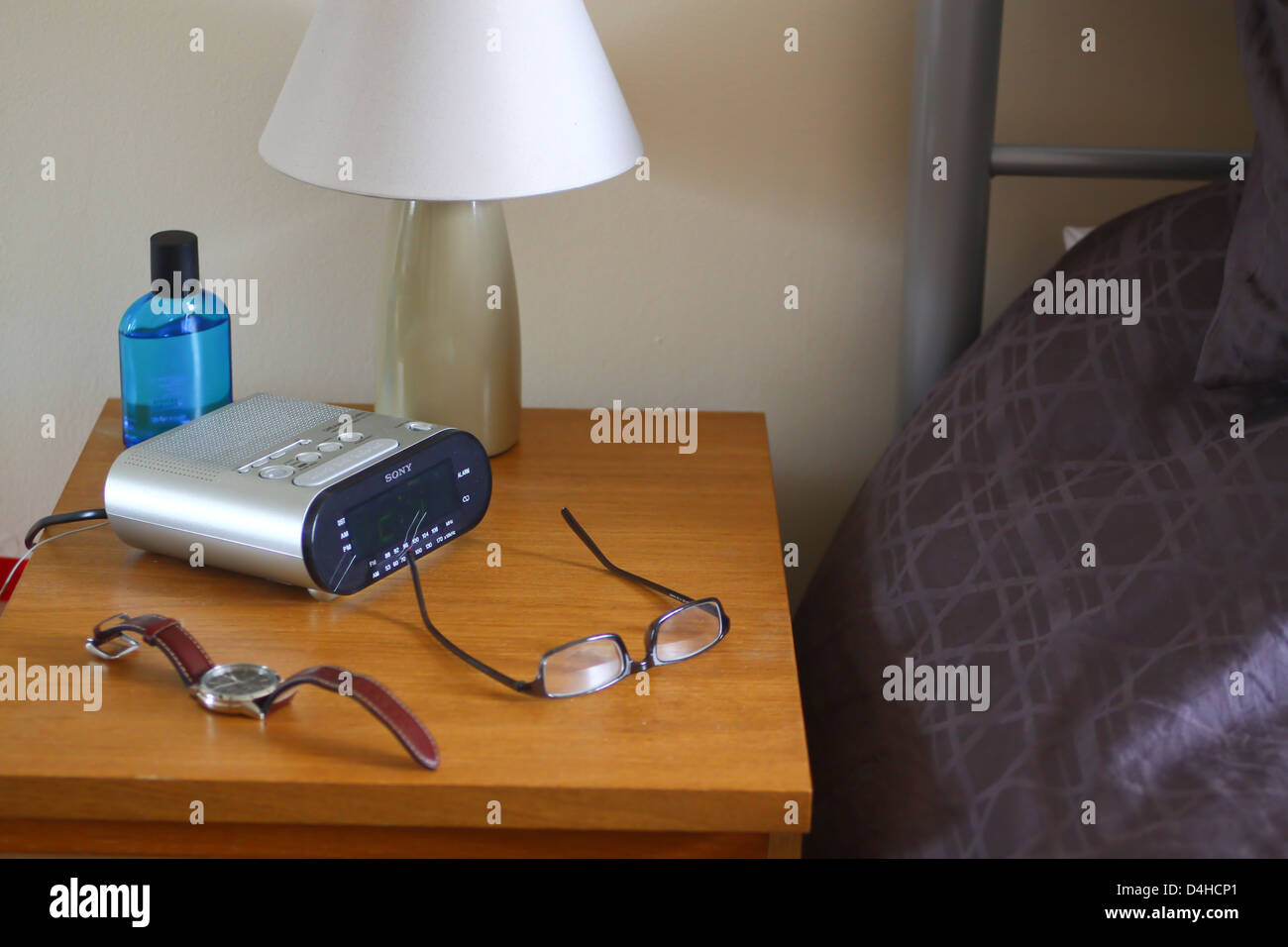 Bedside table with lamp clock radio watch and specs stock photo bedside table with lamp clock radio watch and specs mozeypictures