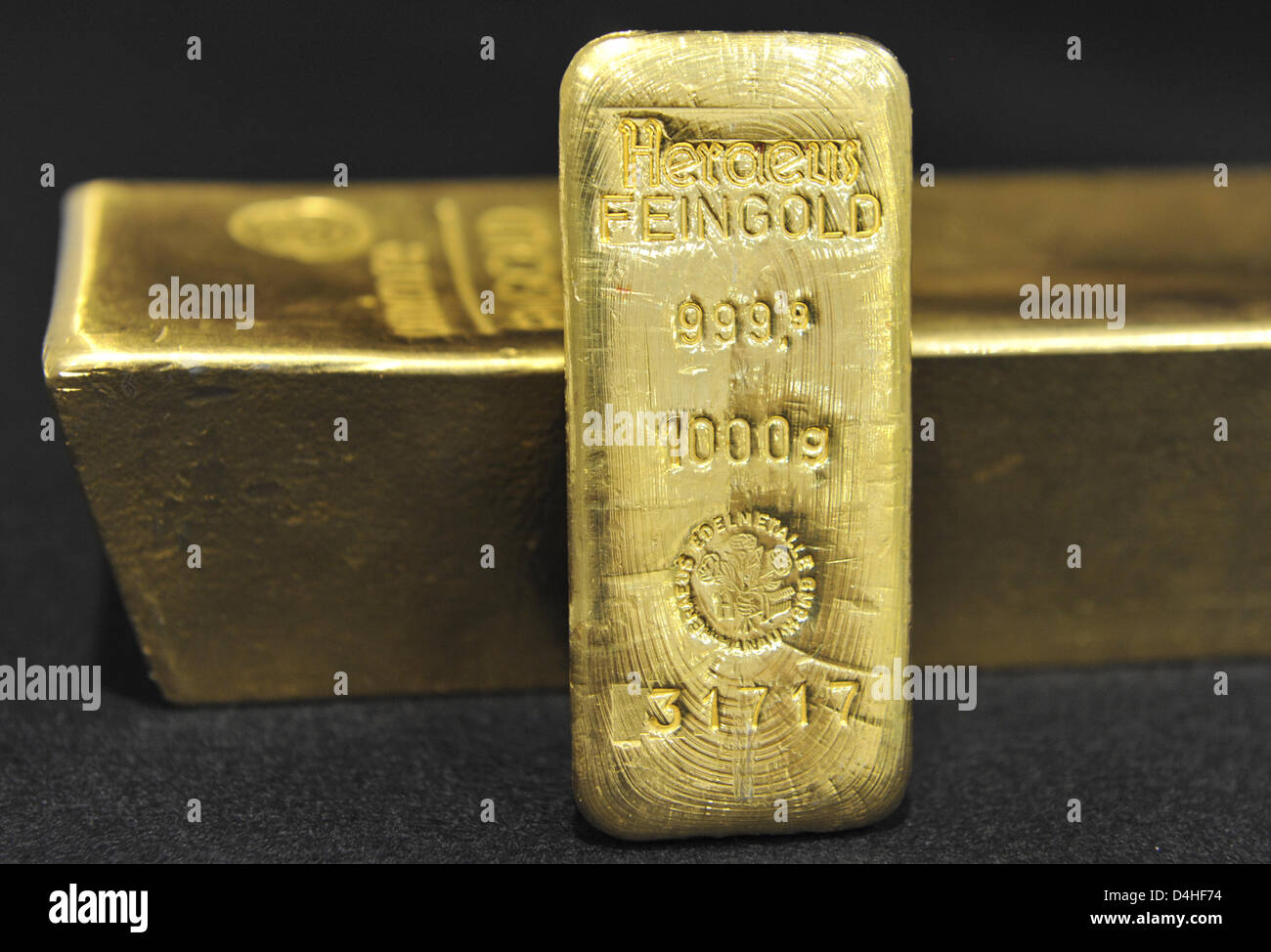 A small bullion weighing 500 grammes is leant against a large gold bar weighing 12 kilogrammes at a bullion dealer - Stock Image