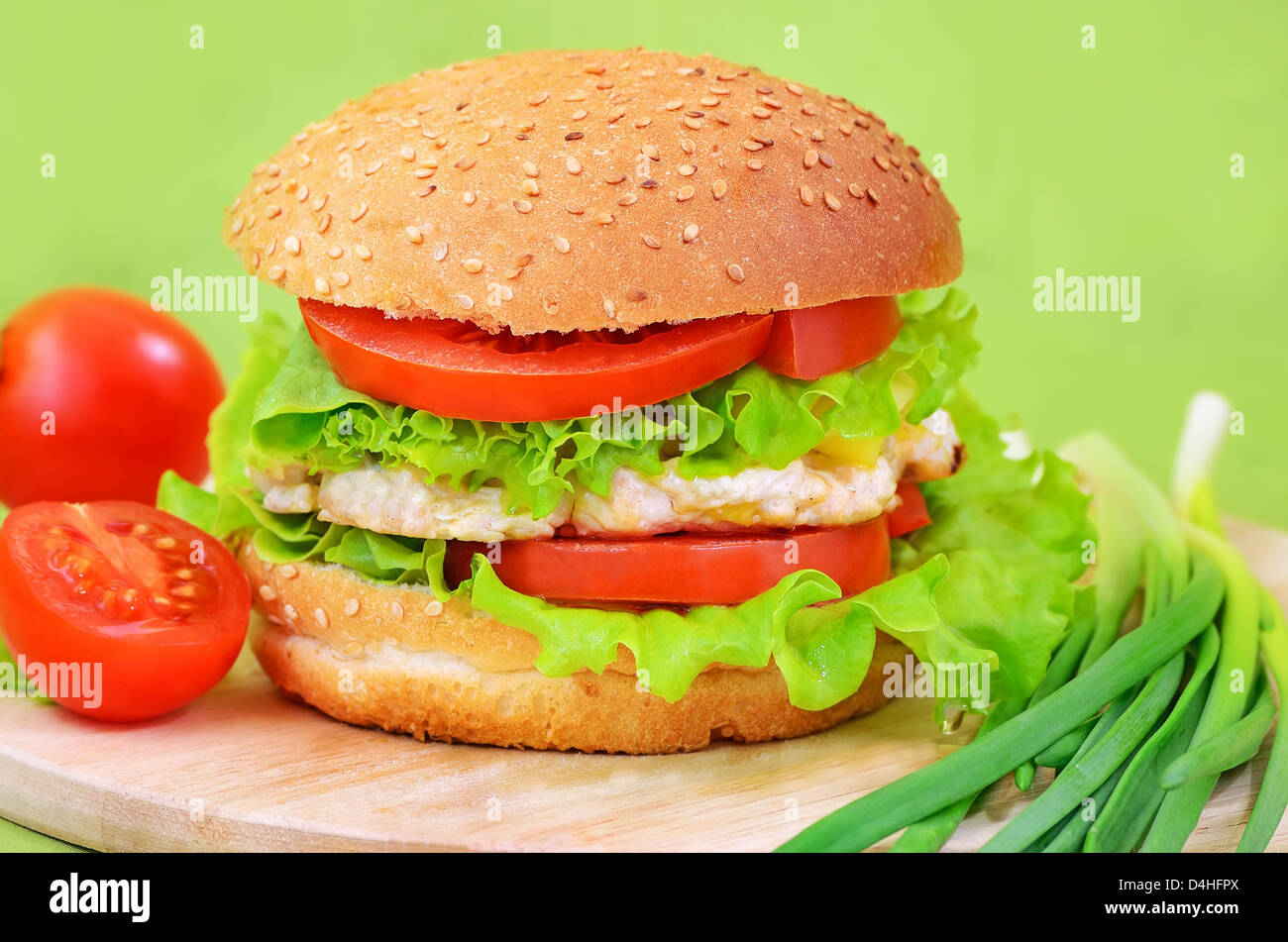 Burger fast food on a kitchen board with tomatoes and green onions - Stock Image