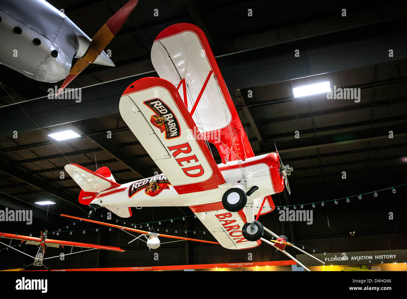 A Red Baron Stearman hands above other exhibits inside the Sun n Fun Florida Air Museum in Lakeland - Stock Image