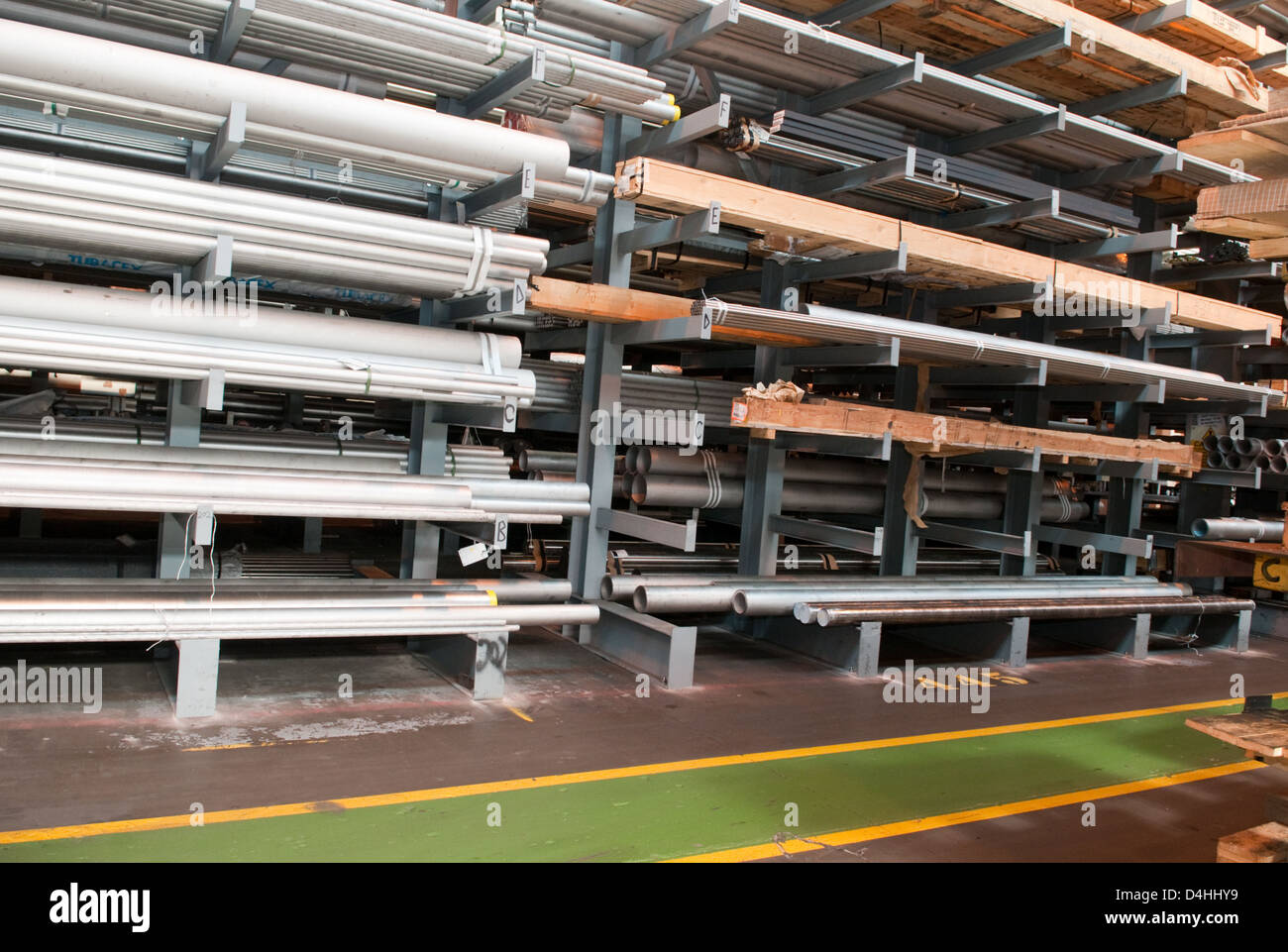 Steel tubes stacked in a warehouse at a steel stock holders in the West Midlands, UK, with a safety walkway painted Stock Photo