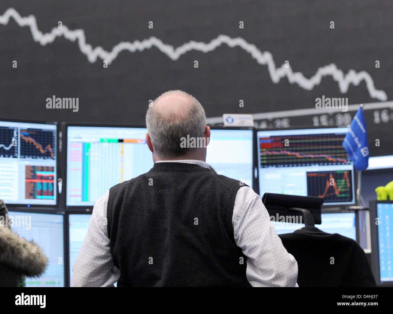 An order book broker observes the indicator board, which shows the