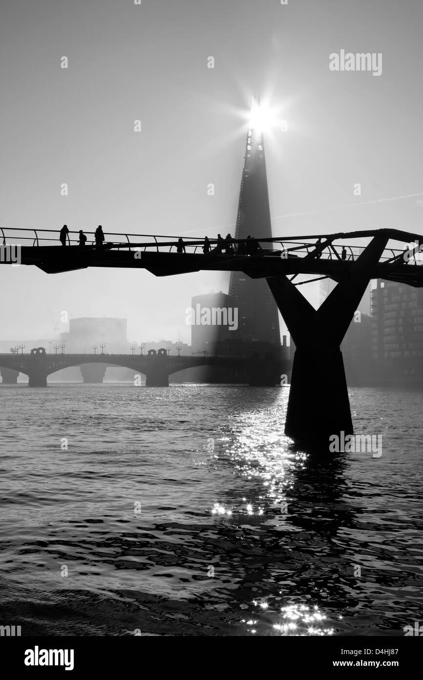 Misty view down the River Thames to the MIllennium Bridge, the Shard and Southwark Bridge, Bankside, UK - Stock Image