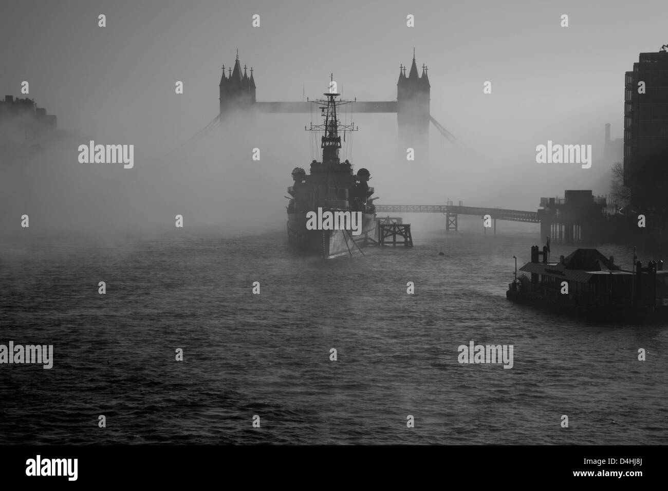 View down the River Thames to a fog-shrouded Tower Bridge and HMS Belfast, City of London, UK - Stock Image