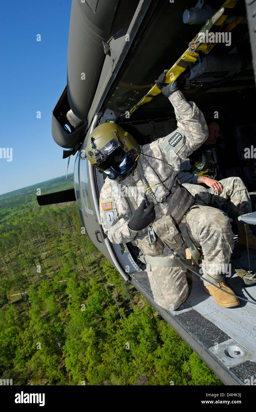 A US Army Ranger views a landing site from the open door of a Black Hawk helicopter during training April 17, 2011 - Stock Image