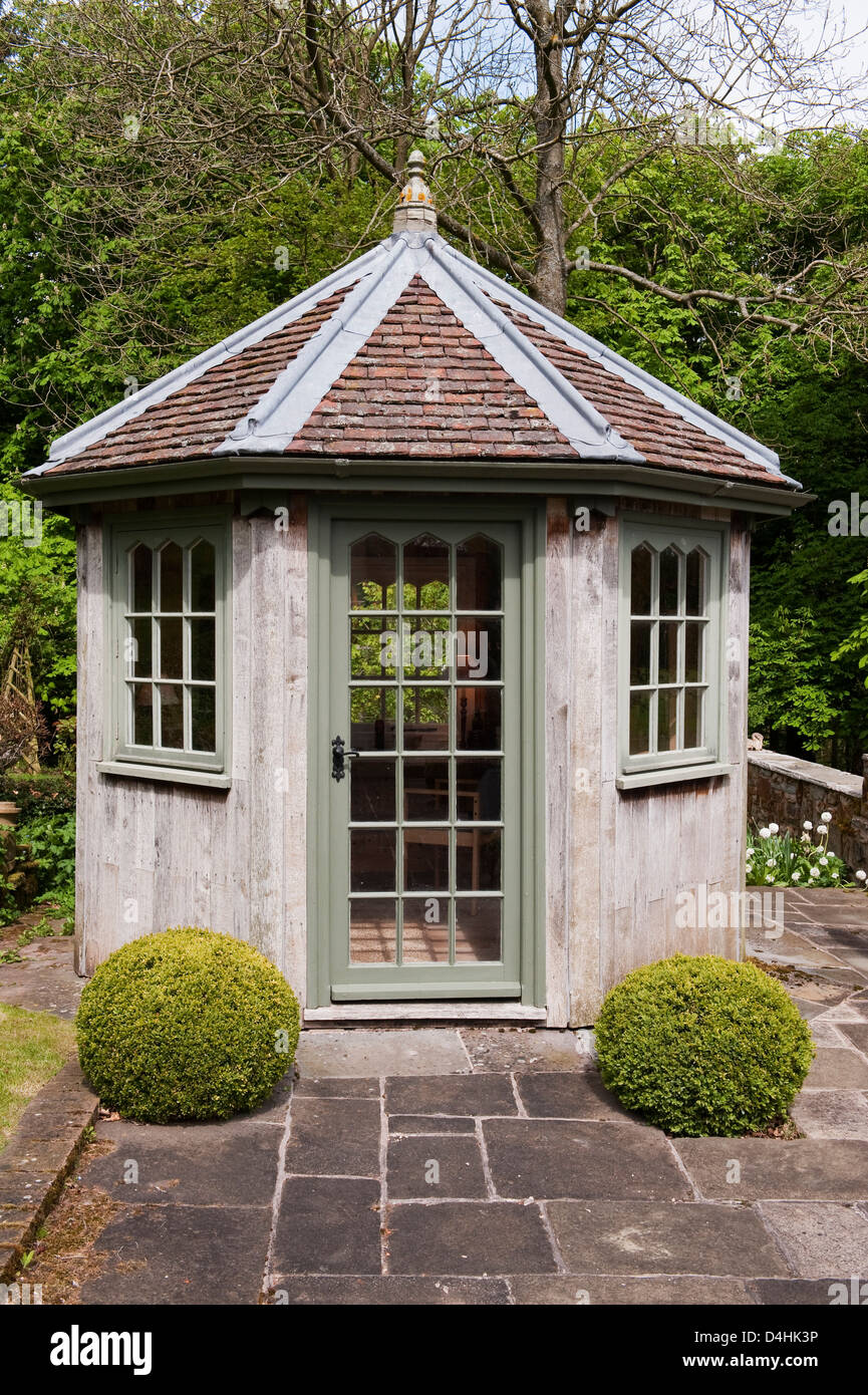A small garden summerhouse, UK. Built in wood with a tiled octagonal roof - Stock Image