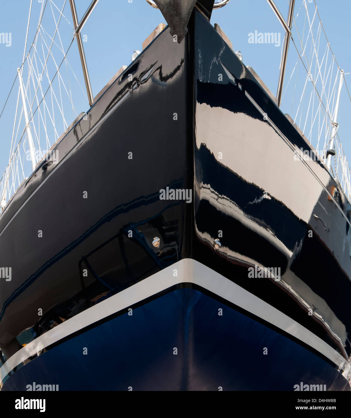 Symmetrical close-up of yacht bow in dark blue glass reinforced plastic with white waterline stripe and blue anti - Stock Image