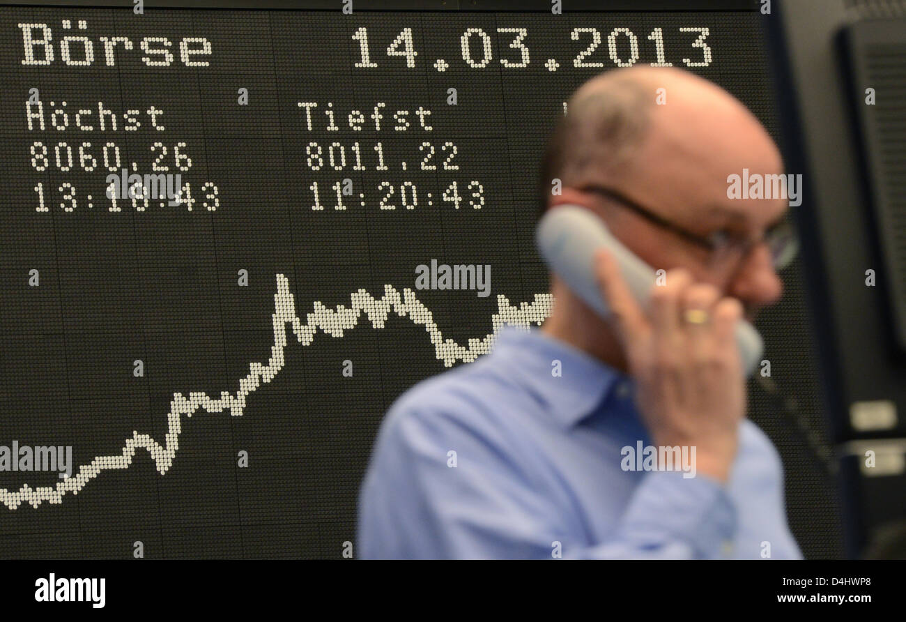 A market specialist talks on the telephone in front of the display with the DAX curve on the trading floor of the - Stock Image