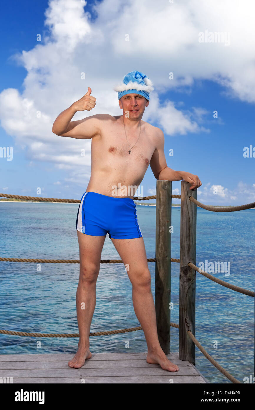 The man in a bathing suit and New Year's Santa-Klaus cap shows a thumb on sea background Stock Photo